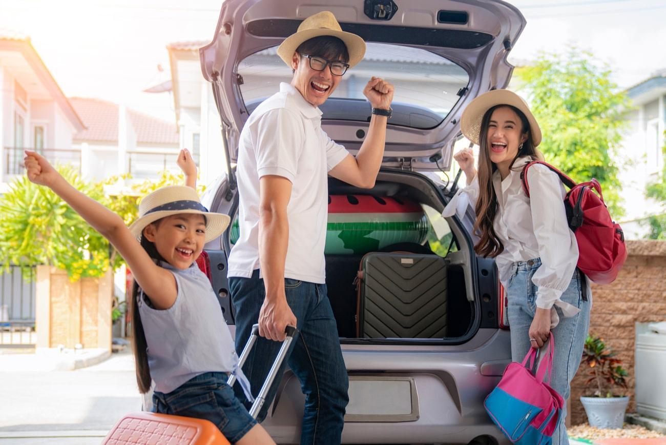 família animada colocando malas dentro do carro para viajar